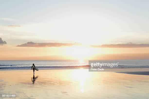 surfer at sunset walking towards sea