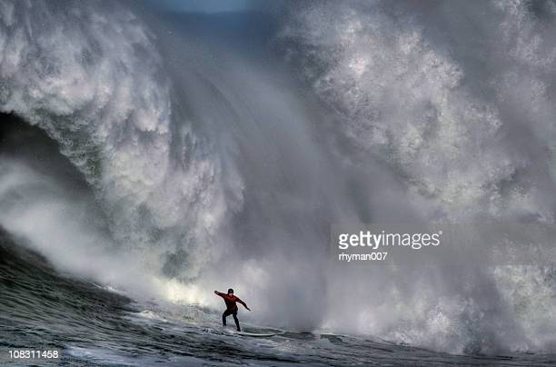 Surfer at the bottom of a huge crashing wave