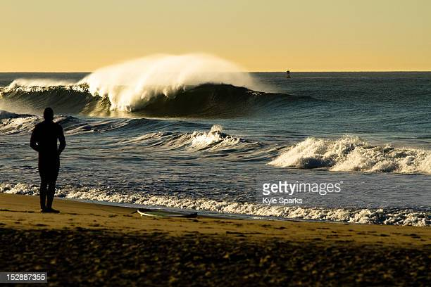 A surfer attaches his leash while watching a large clean wave break in Oxnard, California on January 4, 2012.
