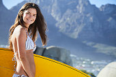 Surfer babe in bikini holding board and smiling at camera