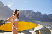 Surfer babe holding surfboard and looking out from beach