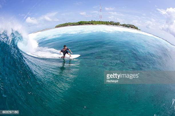 Surfer bottom turns a tropical wave