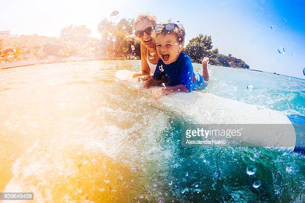 Surfer boy and his mom having fun in the sea