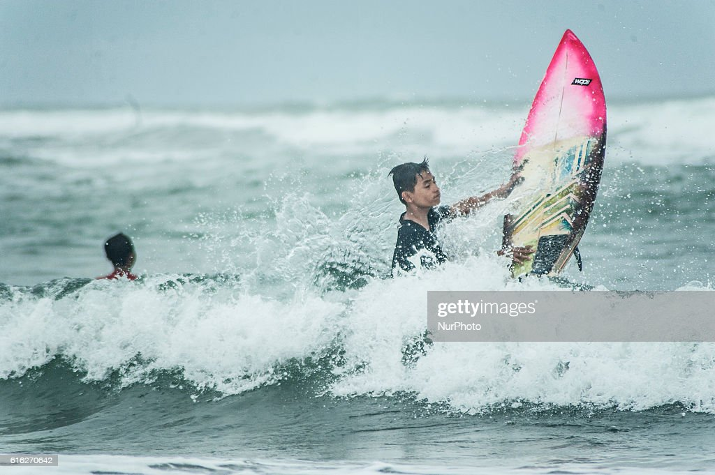 A surfer boy surfing in Parangtritis Beach, Yogyakarta, Indonesia, on October 21, 2016. Despite high waves because of bad weather in Indonesia, Doplhin Parangtritis Surf Community keep surfing and this sport is quite interested by children and adults