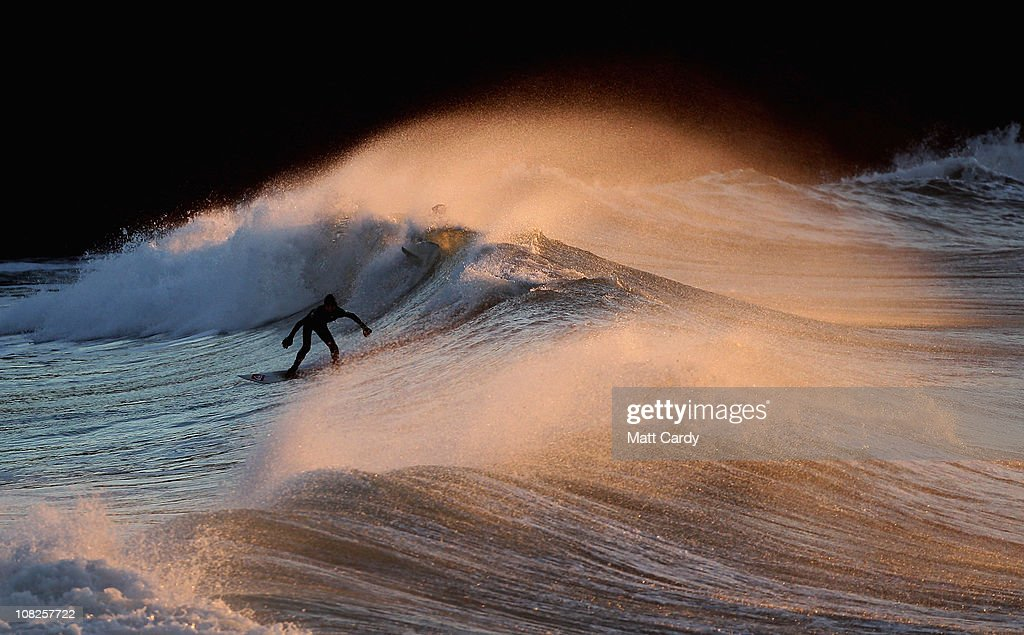 A surfer braves the cold to take advantage of the Cornish winter waves on January 20 2011 in Polzeath England Improved wetsuit materials and...