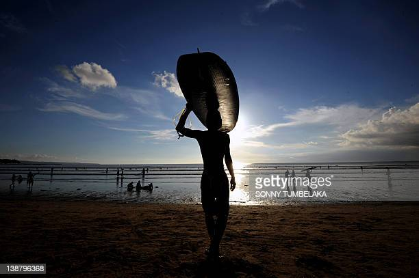 A surfer carries a surf board at Kuta beach on Bali island on February 12 2012 The beauty of Bali allures thousands of tourists every month making...