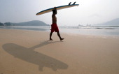 A surfer carries his board on a beach outside of Sanya toward the waters of the South China Sea on October 24 on the southeast coastline of China's...