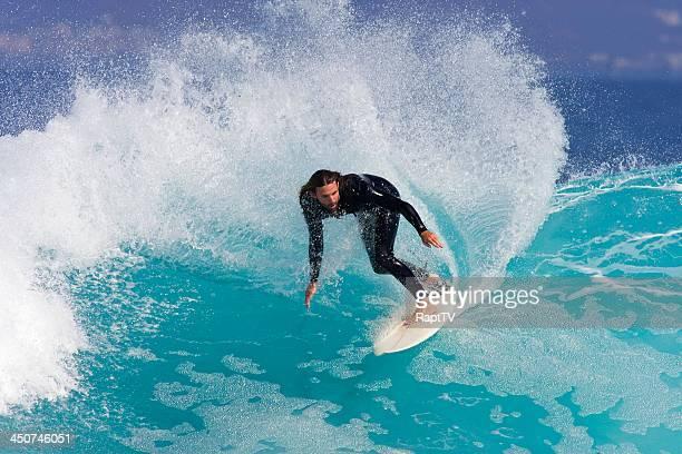 Surfer carve stunning blue wave