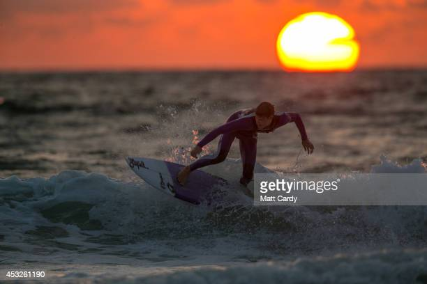 A surfer catches a wave as the sun sets on Fistral Beach on the first day of the Boardmasters surf and music festival in Newquay on August 6 2014 in...
