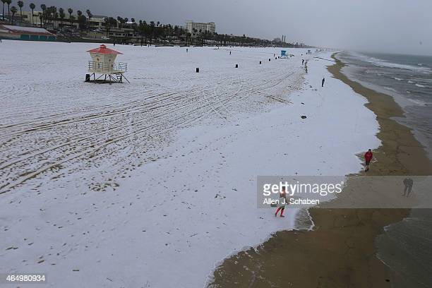 Surfer Derek Peters of Huntington Beach walks across a rare blanket of hail on his way to surf March 2 2015 in Huntington Beach California The...