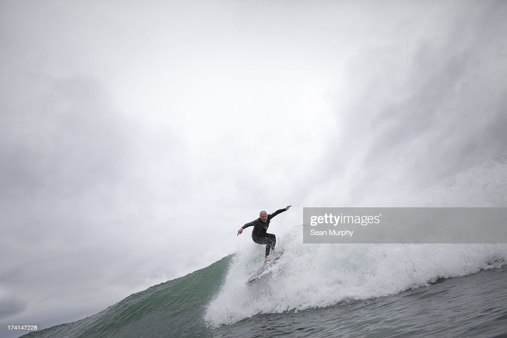 Surfer dropping in to wave : Stock Photo