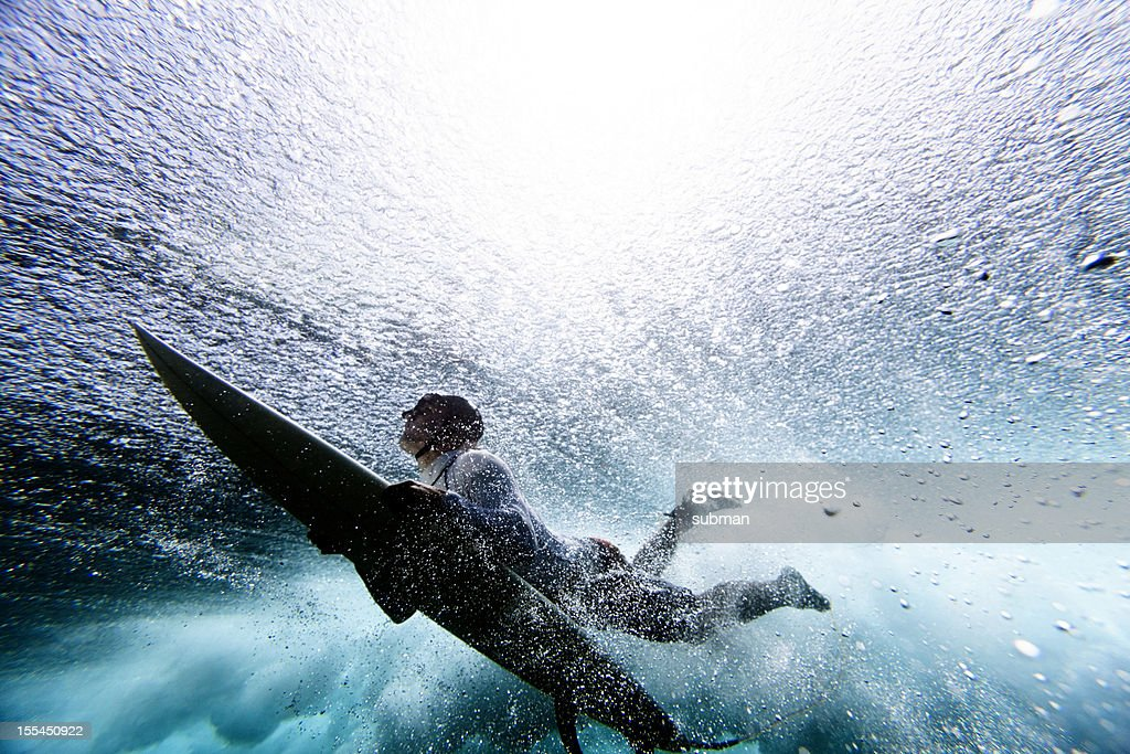 Surfer duck diving : Stock Photo