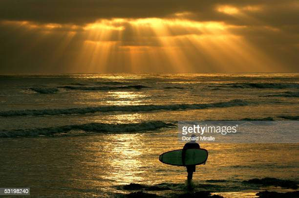 Surfer Ed Folsom exits the water as the sun sets through low clouds on June 23 2005 at Cardiff State Beach in CardiffByTheSea California