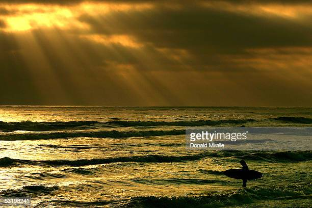 A surfer enters the water as the sun sets through low clouds on June 23 2005 at Cardiff State Beach in CardiffByTheSea California
