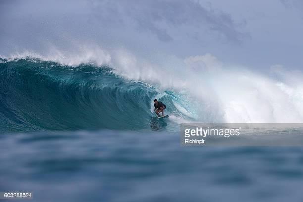 Surfer gets a barrel on a big wave