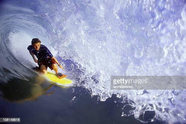 Surfer getting barreled on ocean wave