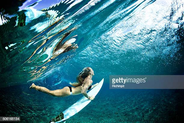 Surfer girl duckdives a wave with reflection