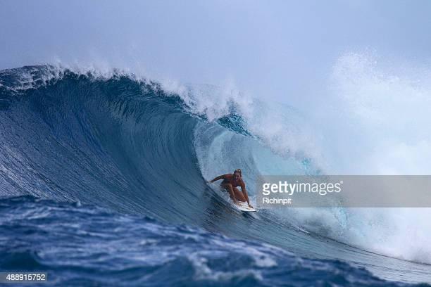 Surfer girl in a big backhand barrel