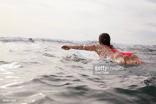 Surfer girl paddling on board