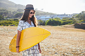 Surfer girl in hat and sunglasses with board, smiling