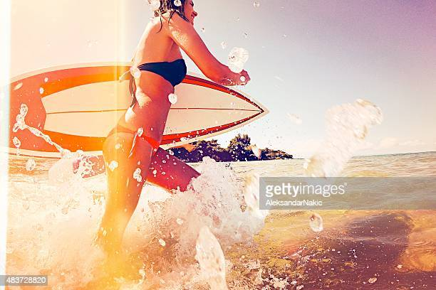 Surfer girl running through the water