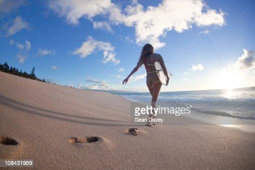 Surfer girl walking along the beach at Ehukai beach park.