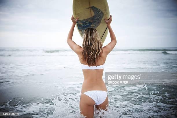 Surfer girl walking in ocean with board