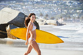 Surfer girl walking to sea with board, smiling