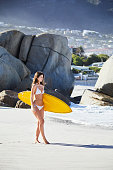 Surfer girl with board on beach, looking away