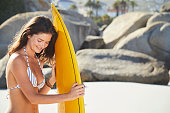Surfer girl with surfboard on beach, smiling