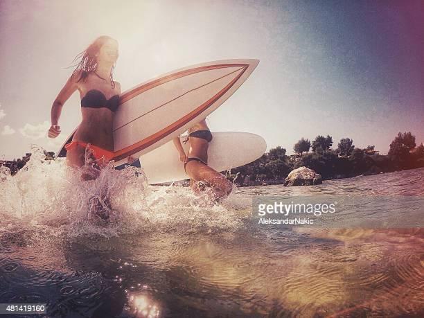 Surfer girls running through the water
