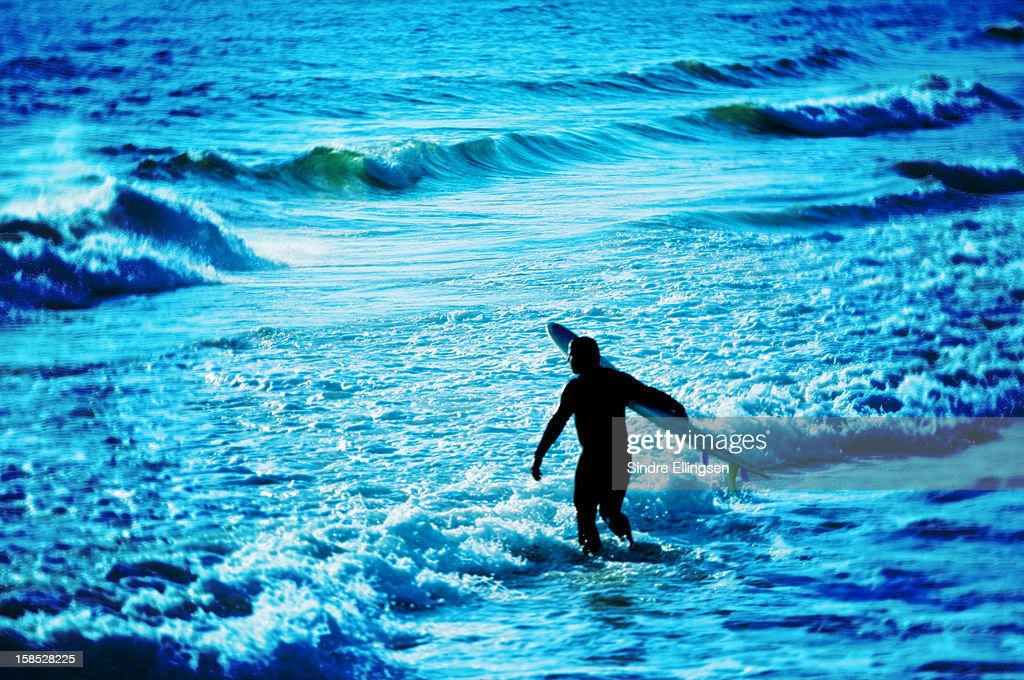 A surfer going into the ocean, Malibu, California : Stock Photo