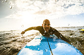 Surfer guy paddling with surfboard at sunset in Tenerife with unrecognizable people at surf boards on background - Sport travel concept with shallow depth of field with drops on lens as composition