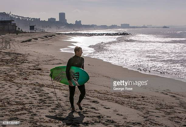 A surfer heads out into the ocean at Will Rogers State Beach on March 3 in Santa Monica Beach California Millions of tourists flock to the Los...