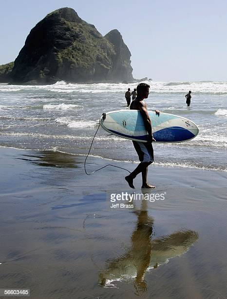 A surfer heads out to the waves as beach goers enjoyed the sun surf and sand at Piha Beach January 17 2006 in Auckland New Zealand