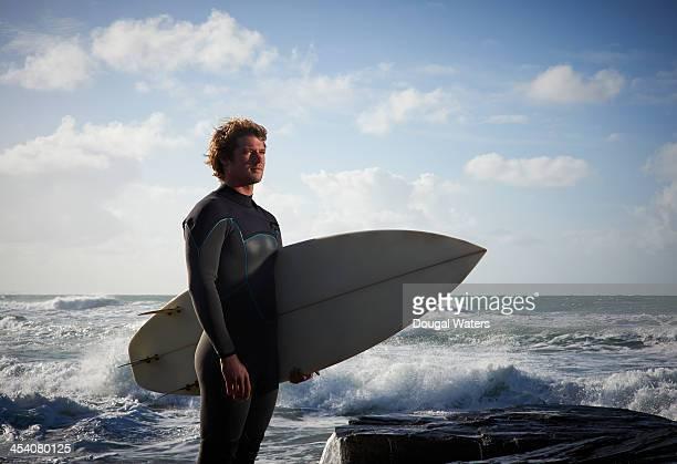 Surfer holding board on coastline.