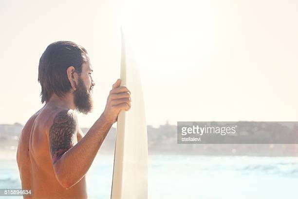 Surfer holding his surfboard at the beach