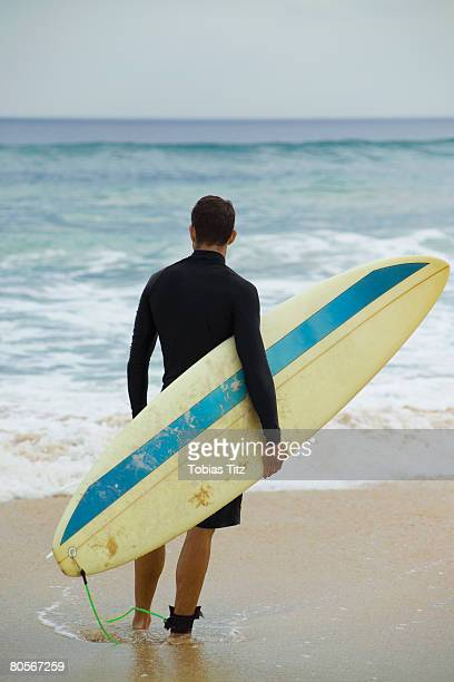 A surfer holding his surfboard