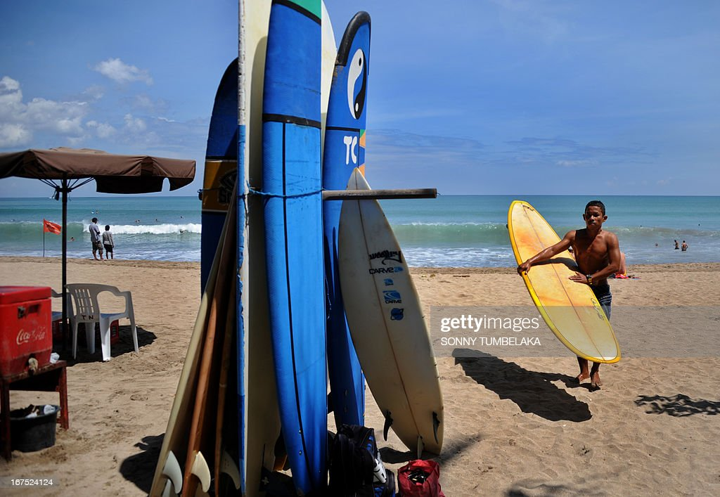 A surfer holds a surfboard at Kuta beach in Bali on April 26, 2013. According to data from the Central Statistics Agency (BPS) in February 2013, the number of foreign tourists arriving in Indonesia increased 14.5 percent to 678,400 at the beginning of the year.