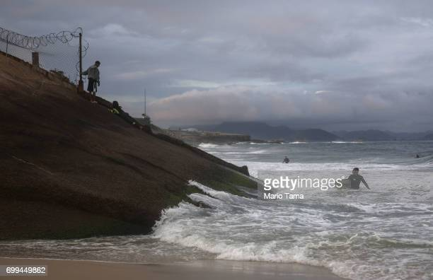 A surfer in a wetsuit prepares to leave Devil's Beach on the first day of winter on June 21 2017 in Rio de Janeiro Brazil Today's solstice marked the...