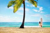 Surfer in Bikini with Surfboard on Palm Tree Tropical Beach
