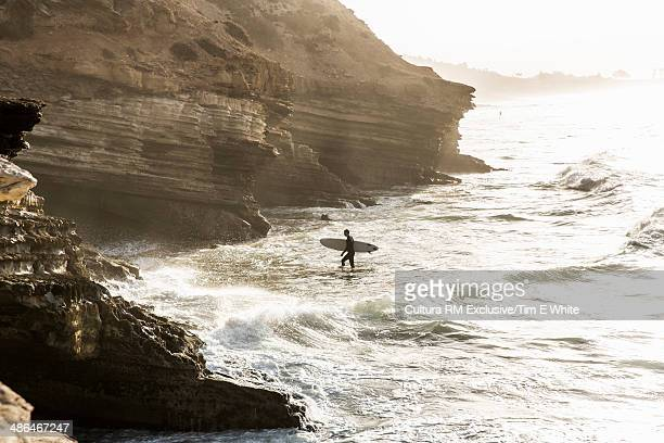 Surfer in sea at sunrise, Taghazout, Morocco