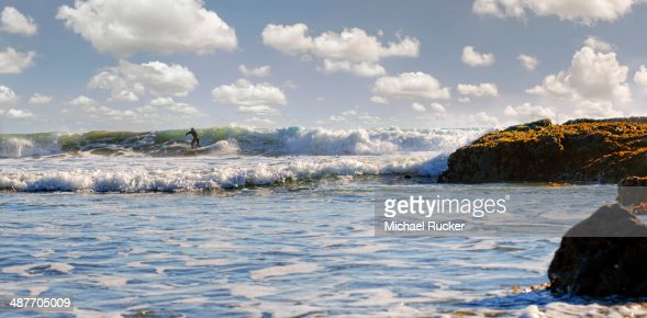 Surfer in the surf on the Pacific beach near Cambria, California, United States