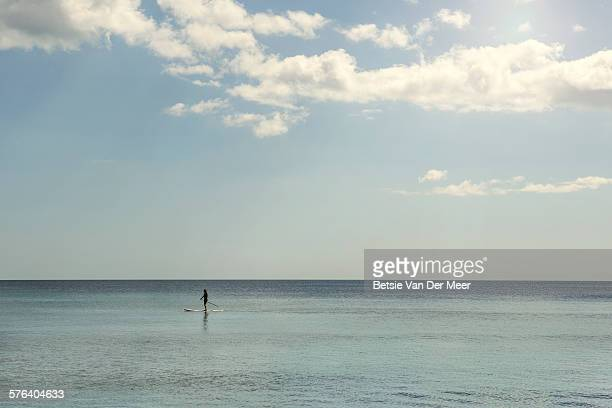 Surfer is paddle boarding along on a calm sea