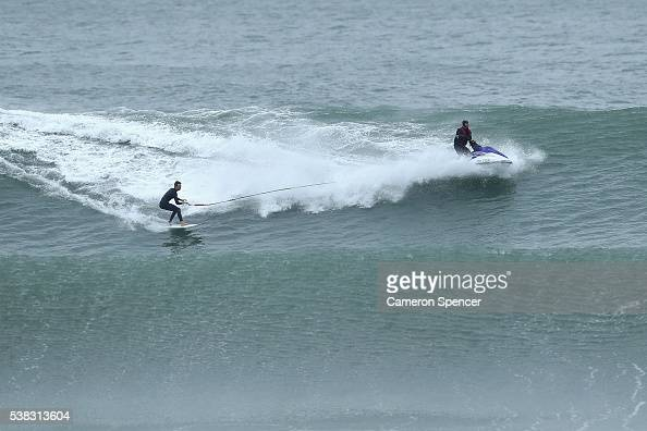 A surfer is towed into a wave at North Narrabeen as large swell hits the Australian East Coast on June 6 2016 in Sydney Australia Torrential rain...