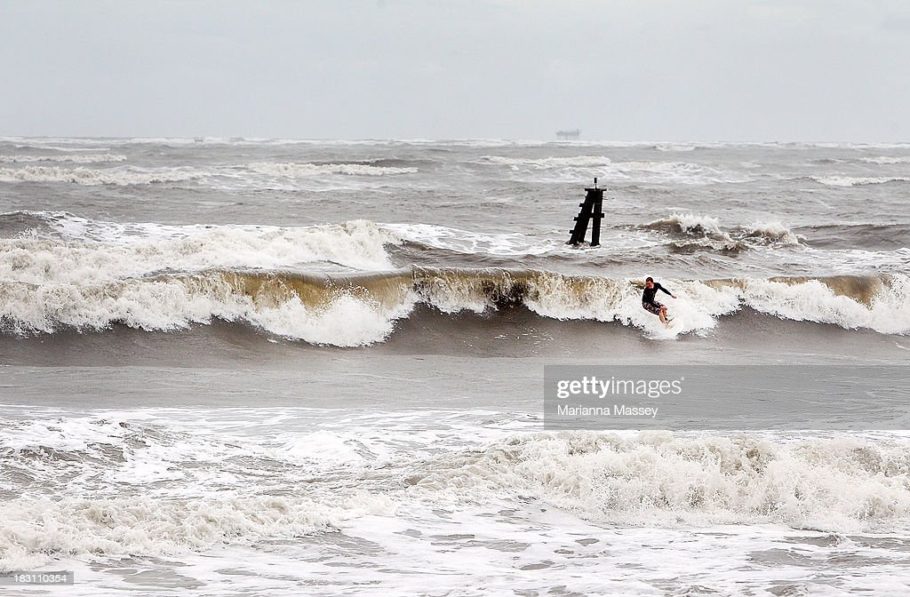 Surfer Jordan Besso braves the rough waters of the Grand Isle pass as winds pick up ahead of Tropical Storm Karen on October 4, 2013 in Grand Isle, Louisiana. Louisiana authorities issued a mandatory evacuation of low-lying areas even as Tropical Storm Karen weakened while moving through the Gulf of Mexico.