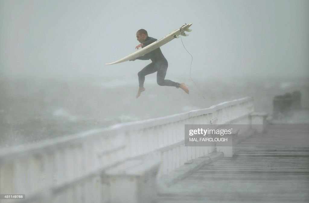 A surfer jumps off the pier into Port Phillip Bay to take advantage of the waves as a storm lashes the Melbourne area on June 24, 2014.