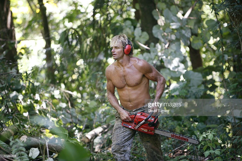 Surfer Laird Hamilton clears trees from his property in Hawaii with a chain saw.