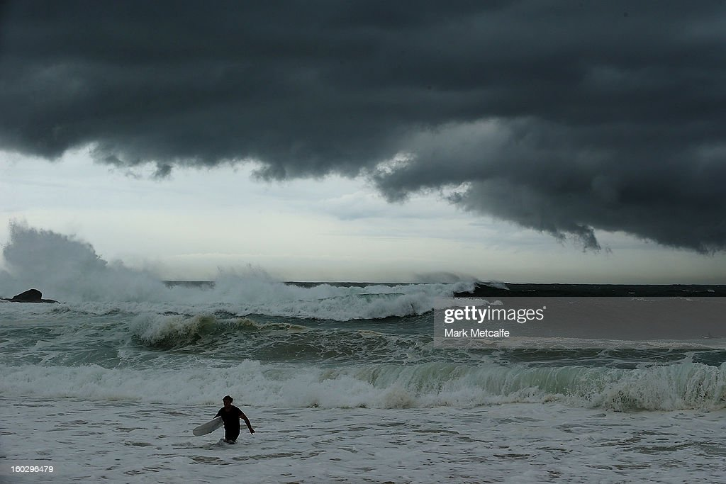 A surfer leaves the water as storm clouds gather at Coogee beach after winds and rain battered Sydney last night on January 29, 2013 in Sydney, Australia. Parts of Sydney are experienced record rainfall after ex-cyclone Oswald swept through the city last night.