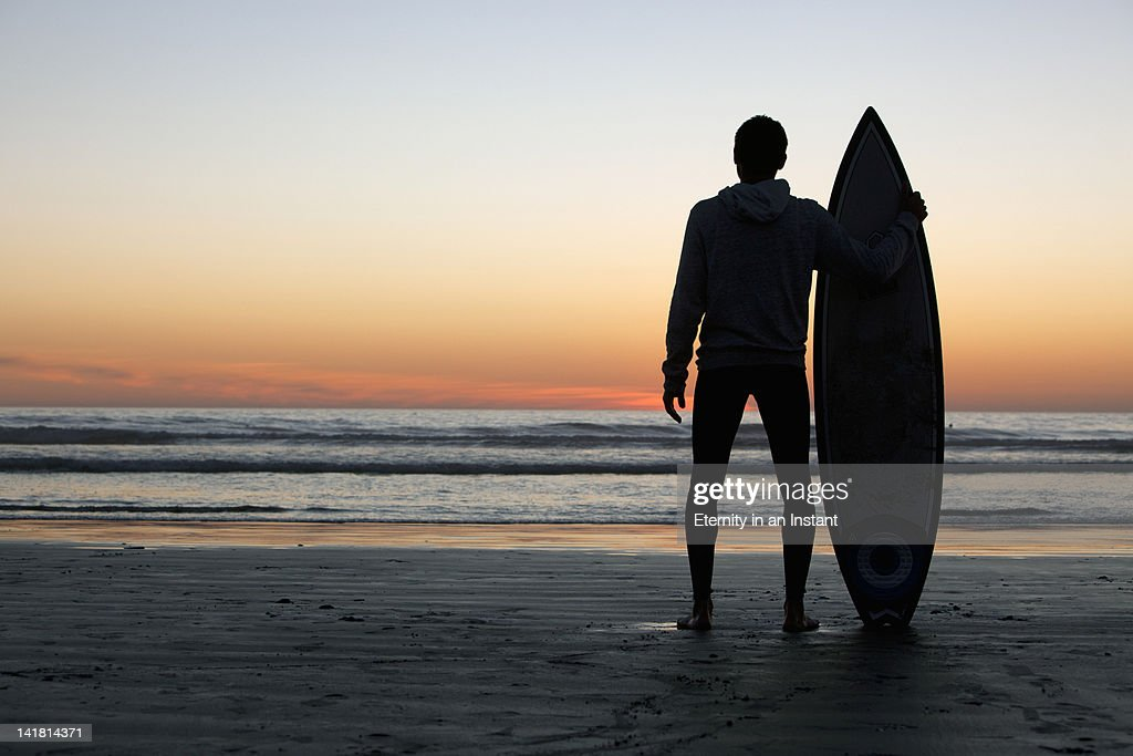 Surfer looking at waves with surfboard at sunset : Stock Photo